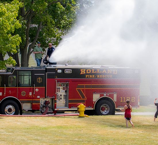 Children playing in water shot from a fire hose
