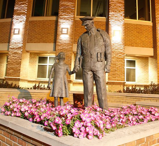 Statue of girl looking up to a police officer